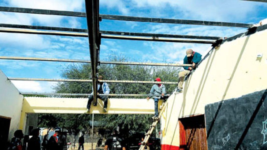 Miembros de La Curvita desarmando la escuela.