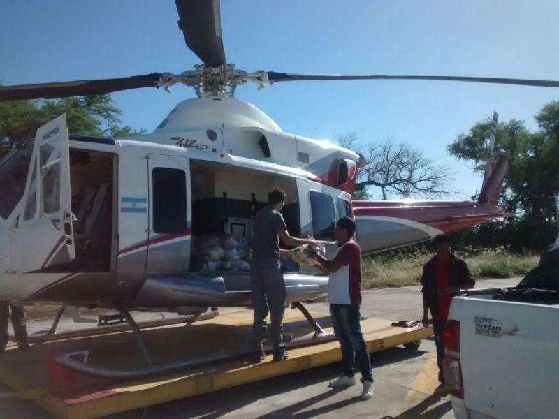 Agentes de Defensa Civil cargan en un helicóptero la ayuda para los parajes aislados ubicados cerca del Río Bermejo.
