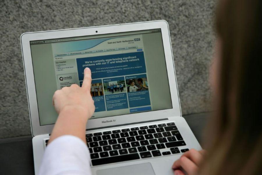 Una mujer señala la página web del NHS, el sistema nacional de salud británico, informando del problema en la red de varios hospitales.