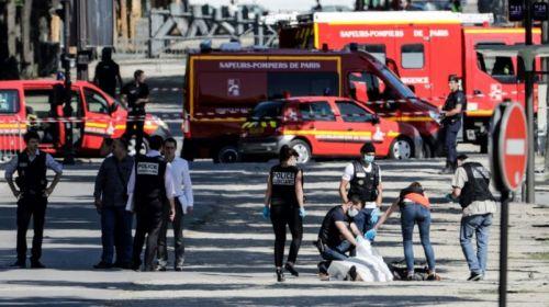 Policías levantan el cuerpo del sospechoso de haber embestido un furgón policial con su vehículo hoyen la avenida de los Campos Elíseos, en París.