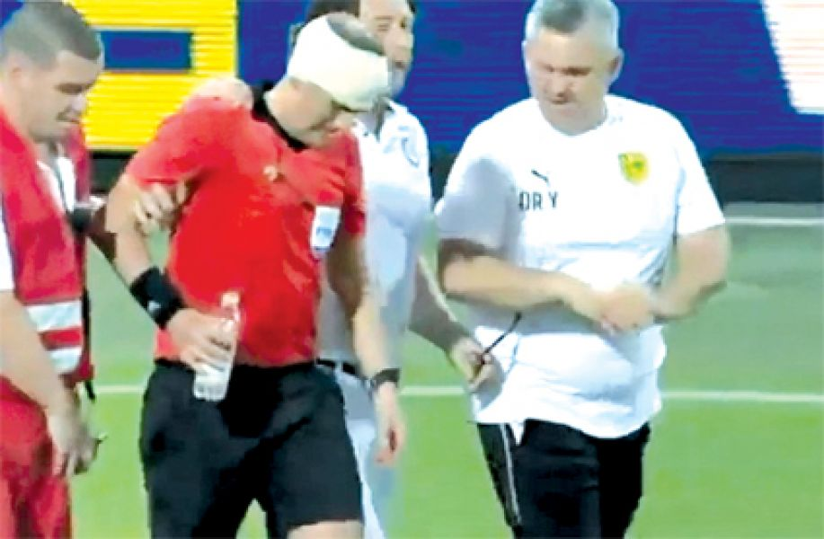 El línea, con un vendaje en la cabeza, es retirado del campo de juego.